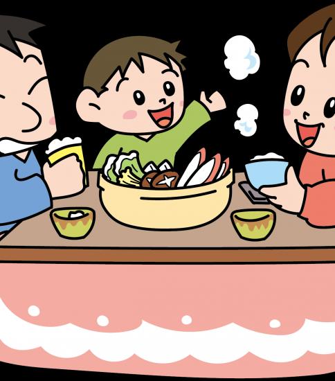 こたつに入りながらカニ鍋を食べる家族